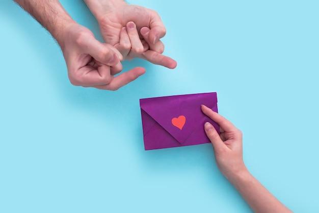 Main de femme holdsenvelope pour la saint valentin et donnez-le à l'homme qui se lève le majeur