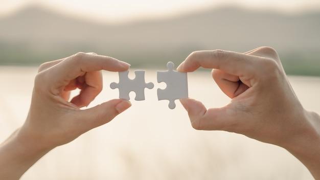 Main de femme et d'homme reliant un morceau de puzzle sur fond de montagne et de lac