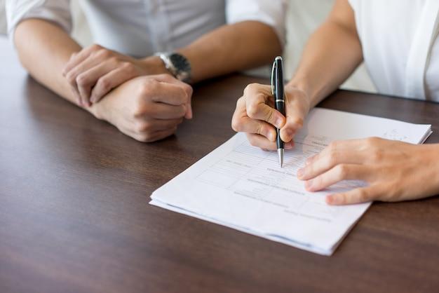 Main de femme hr gestionnaire remplissant le formulaire à l'entrevue avec un candidat masculin.