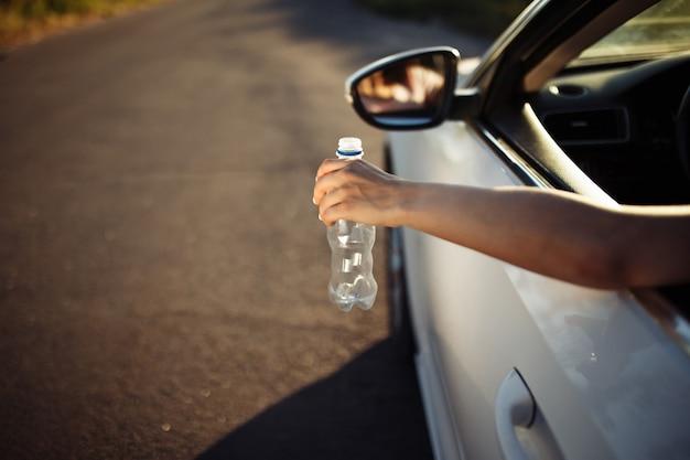 Main de femme jetant une bouteille en plastique par la fenêtre de la voiture.
