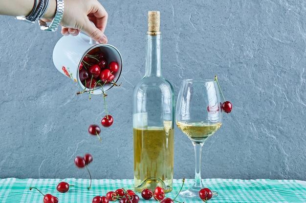 Main de femme jetant une tasse de cerises et une bouteille de vin blanc avec verre sur surface bleue