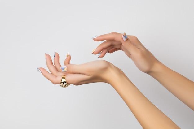 Main de femme jeune adulte avec des ongles à la mode sur fond blanc. conception des ongles printemps été. manucure, concept de salon de beauté pédicure.