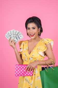 Main de femme jeune fashion holding portefeuille et sacs à provisions