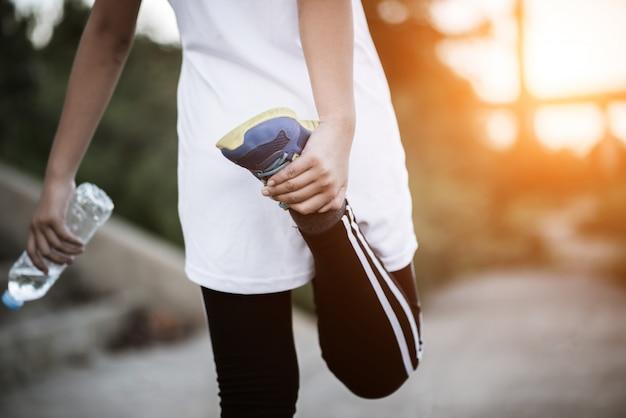 Main de femme jeune de remise en forme tenant la bouteille d'eau après l'exercice en cours d'exécution