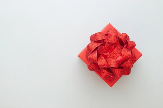Main de femme laïque créative tenant une belle boîte cadeau rouge sur fond de couleur pastel