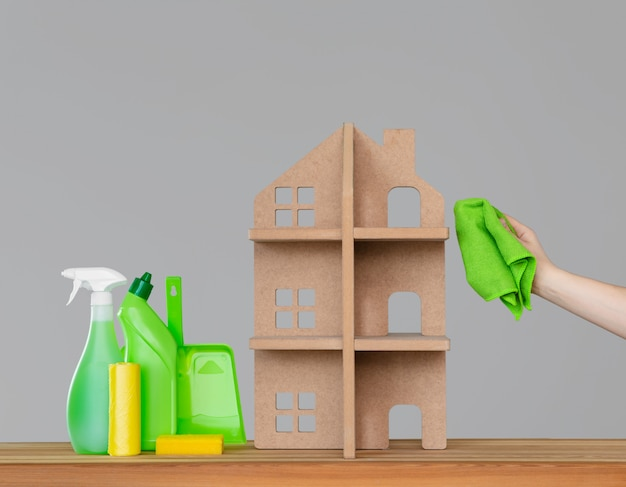 Une main de femme lave la maison symbolique avec un drap vert, à côté de la maison - un ensemble coloré d'outils de nettoyage.