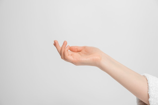 La main d'une femme levée, paume vers le haut, dans le cadre fait partie de la robe.
