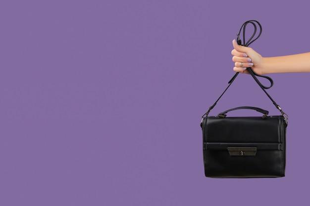 Main de femme avec manucure lavande holding bag sur fond violet