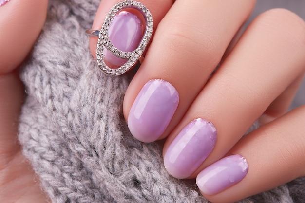 La main de la femme avec la manucure à la lavande à la mode, la conception des ongles de noël d'hiver