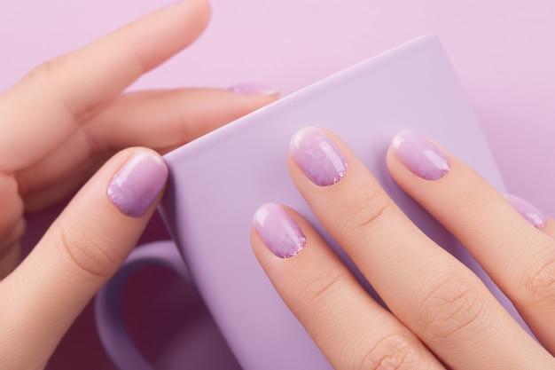 Main de femme avec manucure à la lavande à la mode printemps été design ongles