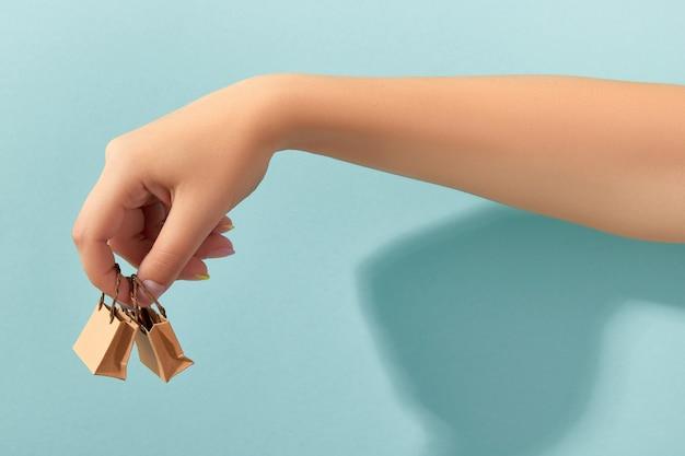 Main de femme avec manucure à la mode tenant de minuscules sacs en papier