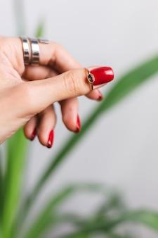 Main de femme avec manucure rouge et deux anneaux sur les doigts, sur une belle feuille de palmier vert tropical. mur gris derrière.