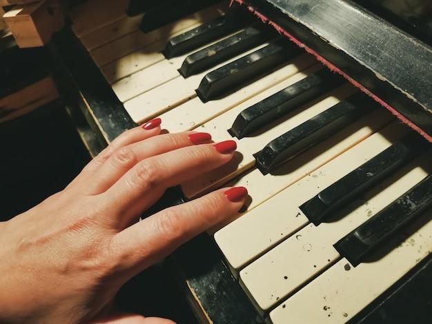 Main de femme avec une manucure rouge sur les touches d'un vieux piano détruit.