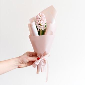 Main de femme avec manucure tenant des fleurs de printemps.
