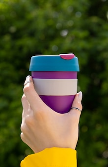 Main de femme avec manucure tenant une tasse réutilisable colorée avec une boisson chaude dans le parc
