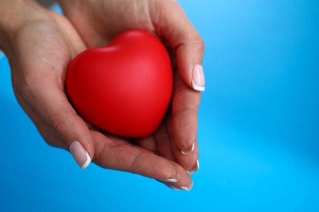 La main de la femme avec manucure tient un coeur