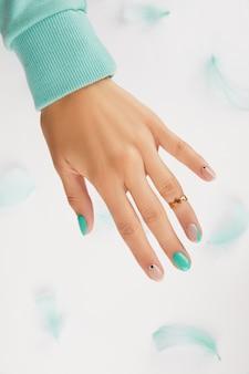 Main de femme avec manucure turquoise à la mode avec espace de copie. tendances de conception de manucure d'été. concept de mode de beauté