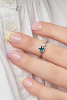 Main de femme manucurée avec des bijoux minimes à la mode