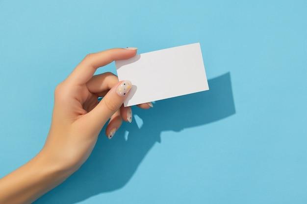 Main de femme manucurée tenant une carte de visite sur fond bleu