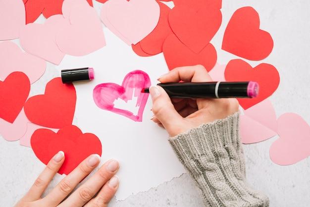 Main de femme avec marqueur peinture coeur près de cartes postales de papier