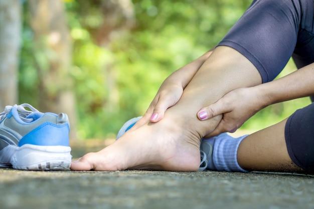 Main de femme massant sa jambe tordue à la cheville cassée