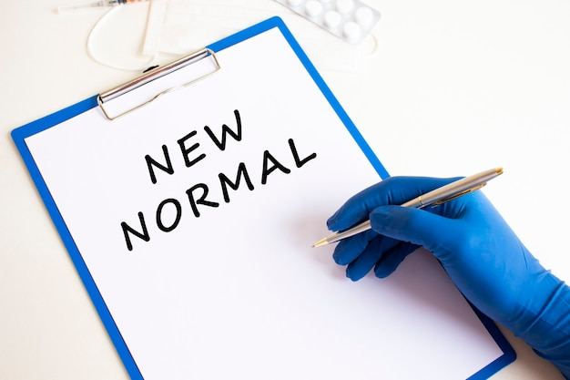 La main de la femme médecin dans un gant médical fait une inscription nouveau normal dans un document. concept médical.