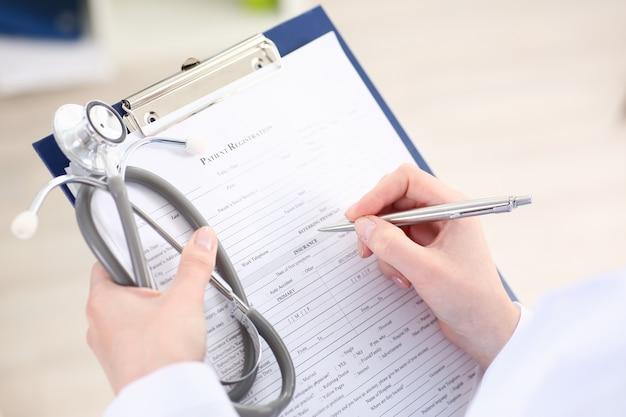 Main de femme médecin détient stylo argenté remplissant la liste des patients au bloc-notes de presse-papiers agrandi.