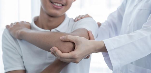 Main de femme médecin faisant de la physiothérapie en étendant l'épaule d'un patient de sexe masculin.