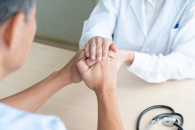 Main de femme médecin tenant sur son patient senior