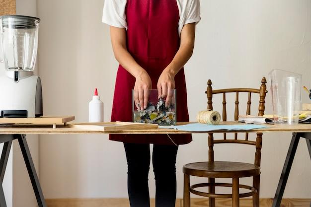 Main de femme mélangeant des papiers déchirés dans l'eau