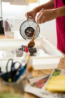 Main de femme mélangeant de la pâte à papier dans l'eau