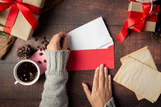 Main de femme met la carte de voeux dans l'enveloppe