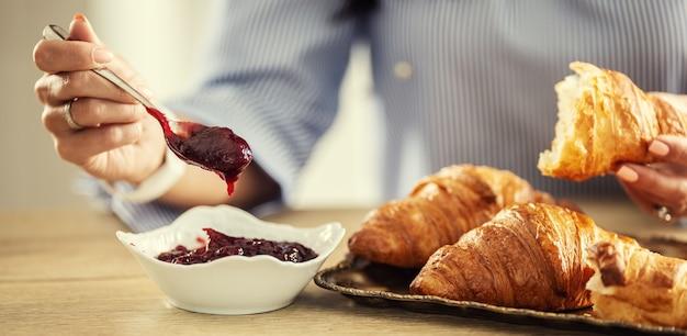 La main de la femme met une cuillère de confiture sur un croissant prenant son petit-déjeuner.