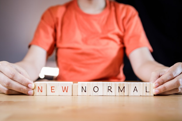 Main de femme mettant des cubes en bois avec concept nouveau ou suivant normal.