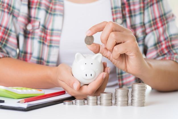 Main de femme mettant la pièce d'argent, concept d'économie d'argent.
