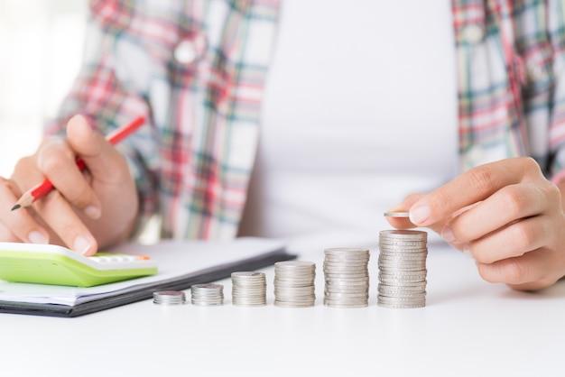 Main de femme mettant la pièce d'argent sur la pile de pièces, économisant de l'argent