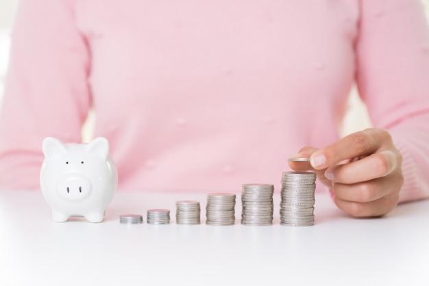 Main de femme mettant une pièce d'argent sur une pile de pièces de monnaie. concept d'économie d'argent.