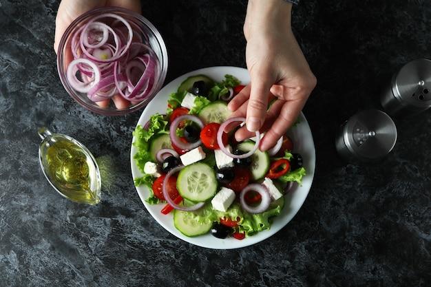 Main de femme mettre des oignons sur une salade grecque sur fond noir smokey