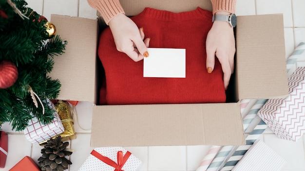 Main de femme a mis la carte de noël dans une boîte cadeau de noël.