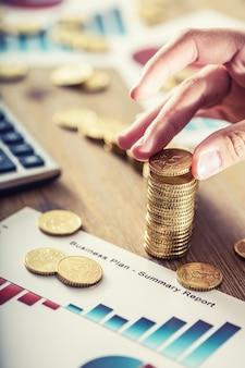 La main de la femme a mis des pièces en euros avec un effet de croissance. nature morte avec cackulator de plan d'affaires et devise euro.