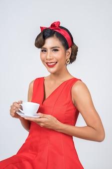 Main de femme de mode heureuse tenant une tasse de café