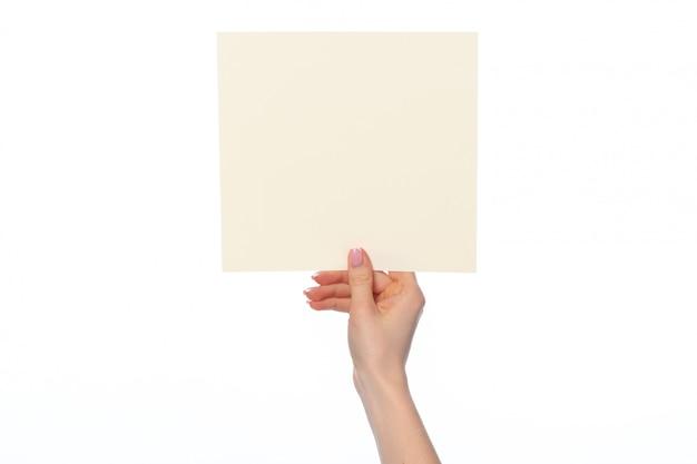 Main de femme montrant une bannière de papier blanc isolé sur blanc