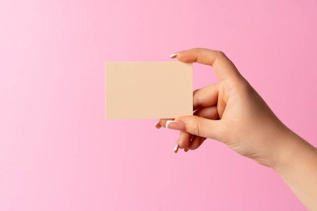 Main de femme montrant une carte de visite vierge sur fond rose.