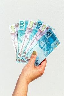 Main de femme montrant cent deux cents factures de reais sur une surface isolée