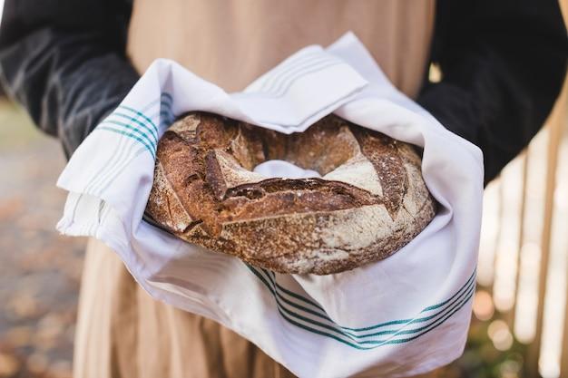 Main de femme montrant du pain bagel rustique en serviette blanche