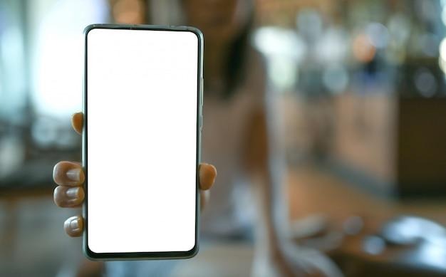 Main de femme montrant l'écran blanc de téléphone portable dans le café.