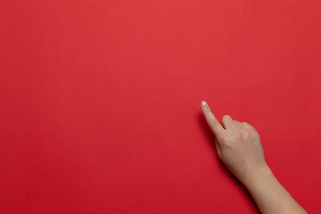Main femme montre la main avec l'index jusqu'à quelque chose de isolé sur fond rouge. composition de style à plat