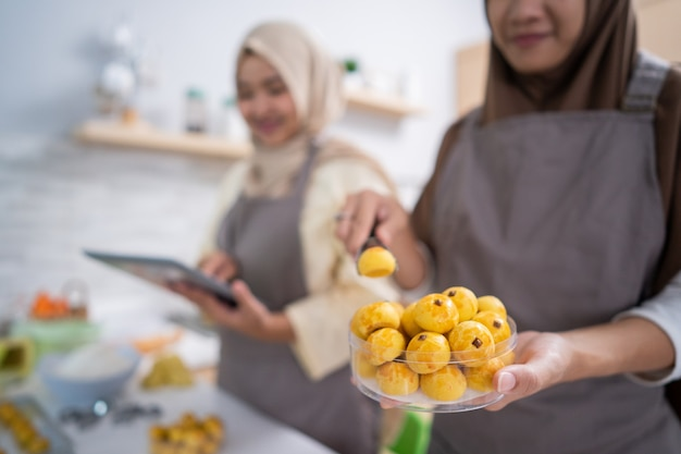 Main de femme musulmane emballant son produit de collation nastar