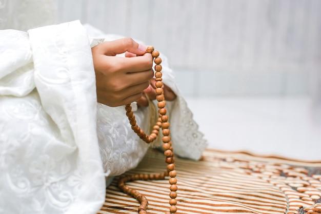 Main de femme musulmane tenant le chapelet pour compter dzikir