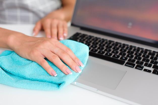 Main femme nettoyant un ordinateur portable à la maison